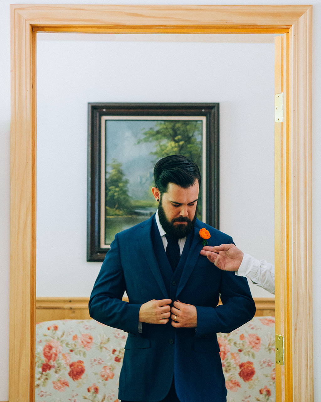 novio vistiéndose en boda en california