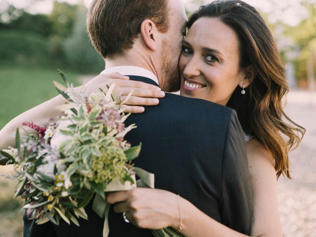novia abrazando con ramo de novia en boda